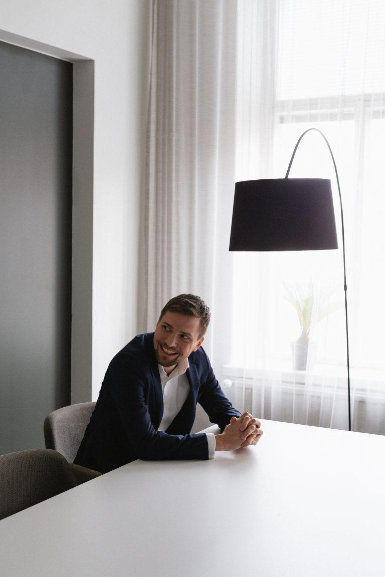 Niilo Mustonen hymyilee Blicin toimistossa.