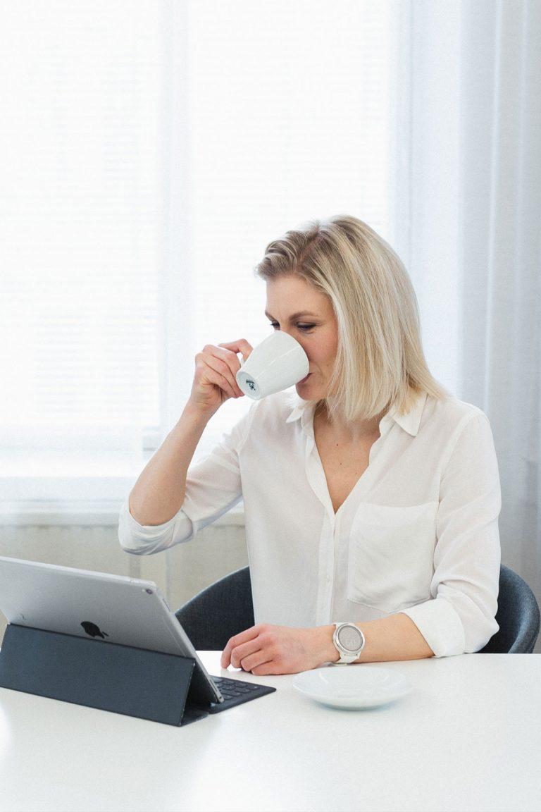 Tiina Fagernäs juo kahvia ja katsoo tietokonetta.